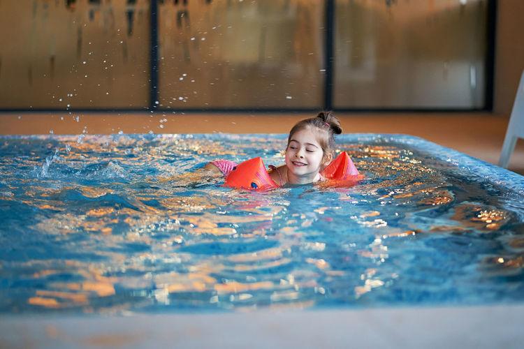 Cute girl swimming in pool