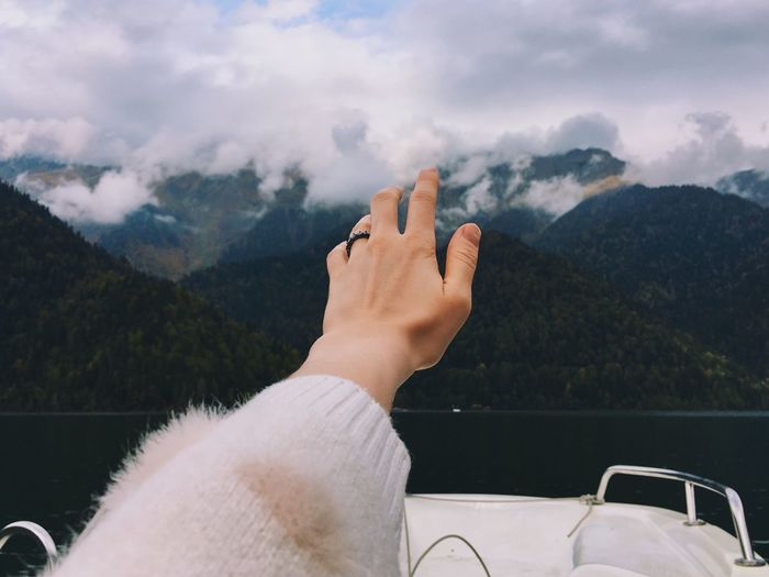 Cropped hand of woman against mountain range against sky