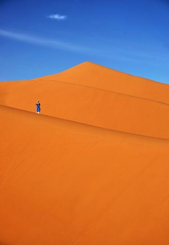 Distant view of person standing at desert