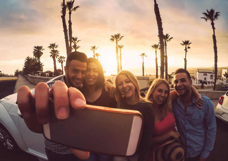 Friends taking selfie during a road trip Convertible Friends Car Happy People Young Adult Youth Cabriolet Smiling Happiness Emotion Technology Group Of People Sunset Togetherness Portrait Real People Communication Young Men Sky Camera Lifestyles Bonding Positive Emotion Outdoors