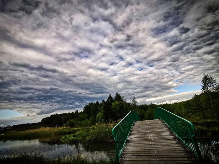 Boardwalk leading towards lake against sky
