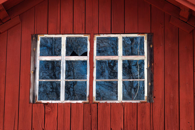 Old house facade with broken window panes from a typical red swedish house