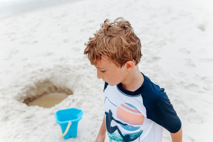 Boy enjoying on sand at beach