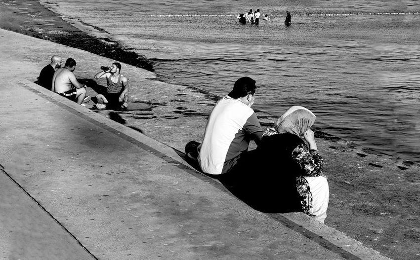 Rear view of people enjoying at beach