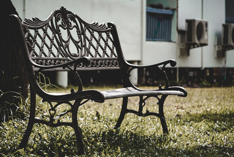 Empty chairs and table in lawn outside house