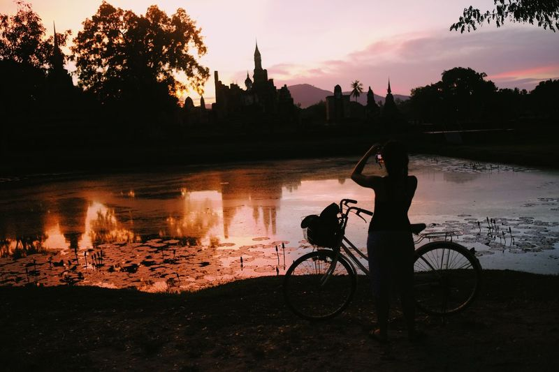 Bicycle Silhouette Real People Sunset Water Outdoors Transportation Tree One Person Men Nature Cycling Sky Mode Of Transport River Leisure Activity Land Vehicle Lifestyles Riverbank Full Length Sukhothai Historical Park Sukhothai
