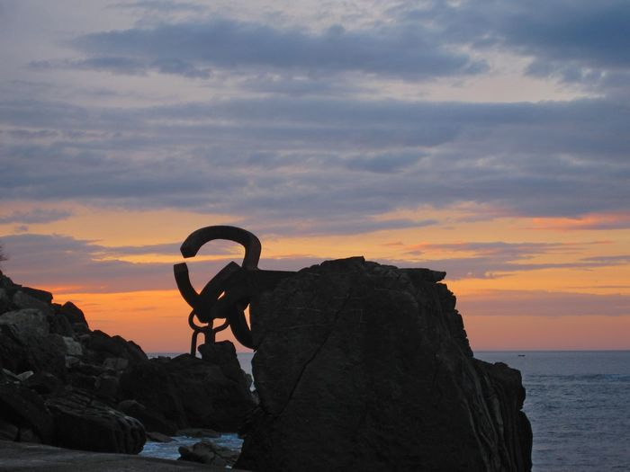 Silhouette man on rock by sea against sky during sunset