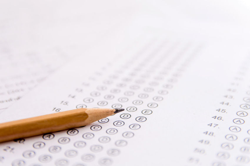 Pencil on answer sheets or Standardized test form with answers bubbled. multiple choice answer sheet Choice Mark Quiz Answer Bubble Class Copy Space Exam Finance Geometric Shape In A Row Indoors  Knowledge Number Paper Pencil Question School Score Selective Focus Sheet Standard Studio Shot Study Test