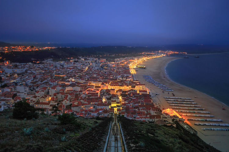 Aerial view of townscape by sea against blue sky at night