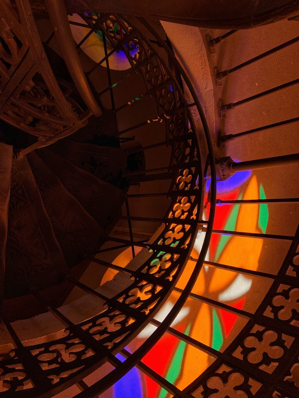 staircase, indoors, steps and staircases, pattern, architecture, spiral, spiral staircase, design, high angle view, no people, railing, multi colored, built structure, flooring, illuminated, shape, geometric shape, tile, building, tiled floor