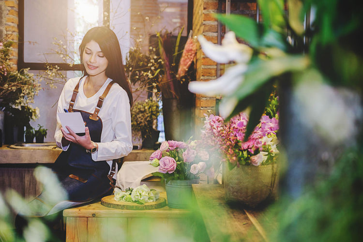 Woman writing in paper while sitting at flower shop