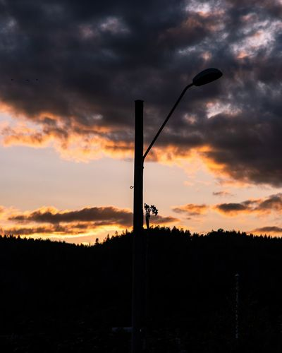 Silhouette street light on field against sky during sunset