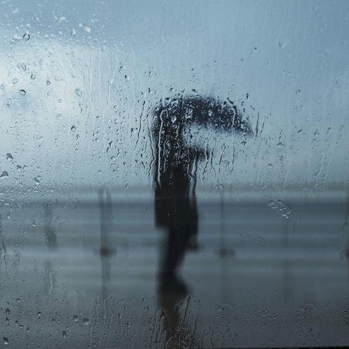 Person seen through wet glass window in rainy season