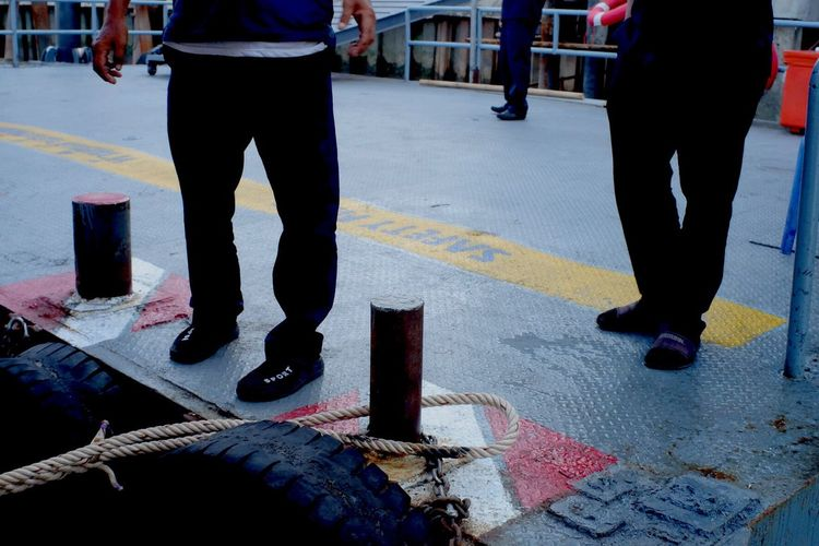 Low section of men by rope at bollard
