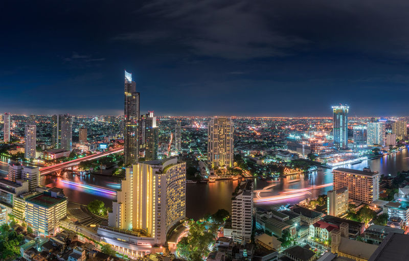Illuminated Buildings Along Chao Phraya River In City Against Sky