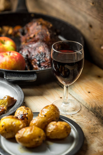 Goose baked with apples, wine and potatoes Wineglass Mediterranean Food Wine Gourmet Main Course Preparation  French Food Roasted Meat Close-up Roast Dinner White Meat Grilled Alcoholic Drink Red Wine Barbecue Grill