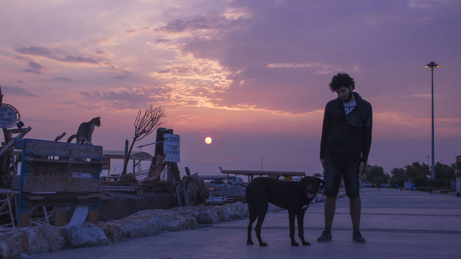 People standing with dog against sky during sunset