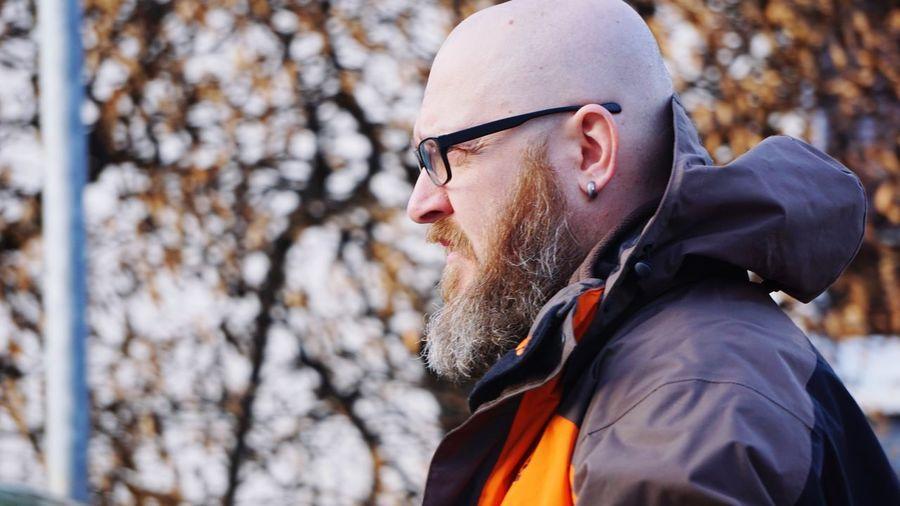 Side view of man wearing eyeglasses against tree
