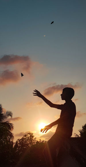 Silhouette man flying against sky during sunset