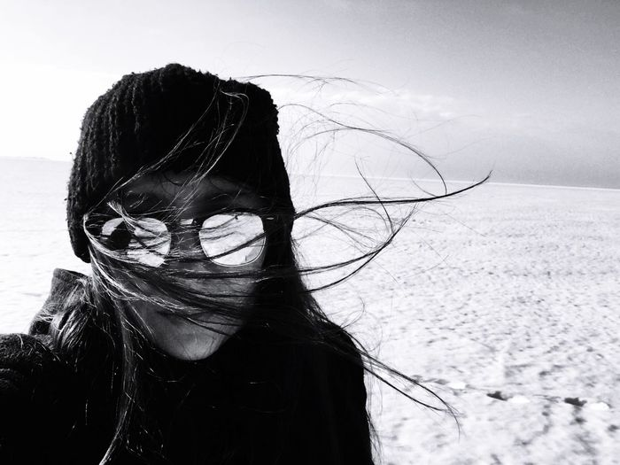Portrait of woman with tousled hair wearing sunglasses and knit hat during winter