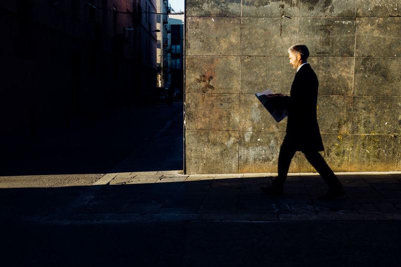 Side View Of Businessman Reading Newspaper While Walking On Sidewalk