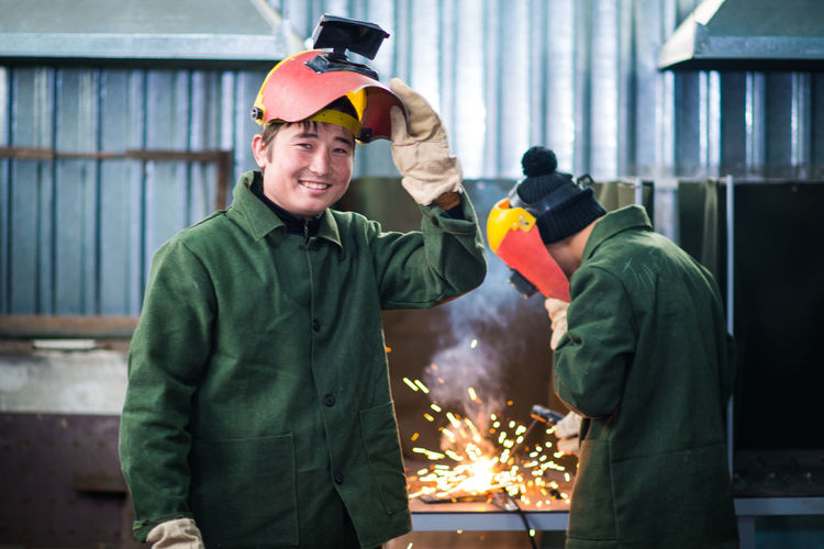 The Modern Professional Two People Men Helmet Coworker Protection Waist Up Occupation Portrait Industry Looking At Camera Smiling Headwear Cooperation Adult Burning Teamwork Standing Safety Motion Males  Kyrgyzstan