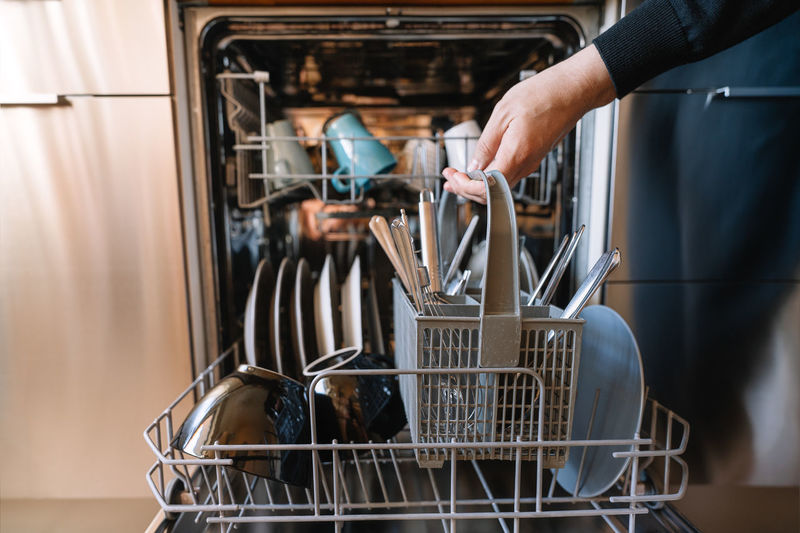 Midsection of man loading dishwasher machine in kitchen at home