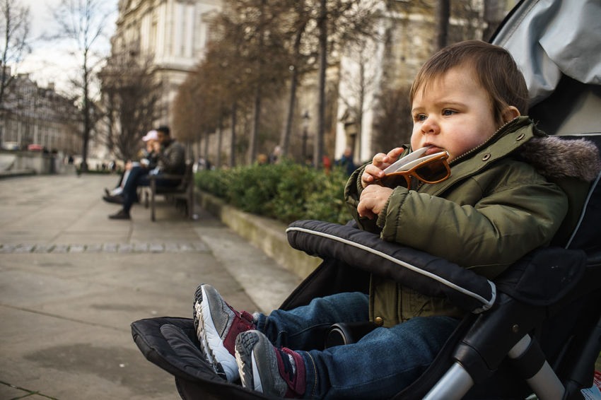 Baby Stroller Casual Clothing Childhood Day Focus On Foreground Land Vehicle Leisure Activity Lifestyles Outdoors Real People Relaxation Side View Sitting Transportation Warm Clothing