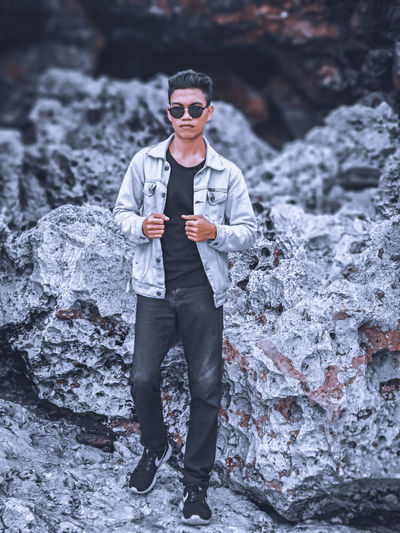 Portrait of young man standing on rock