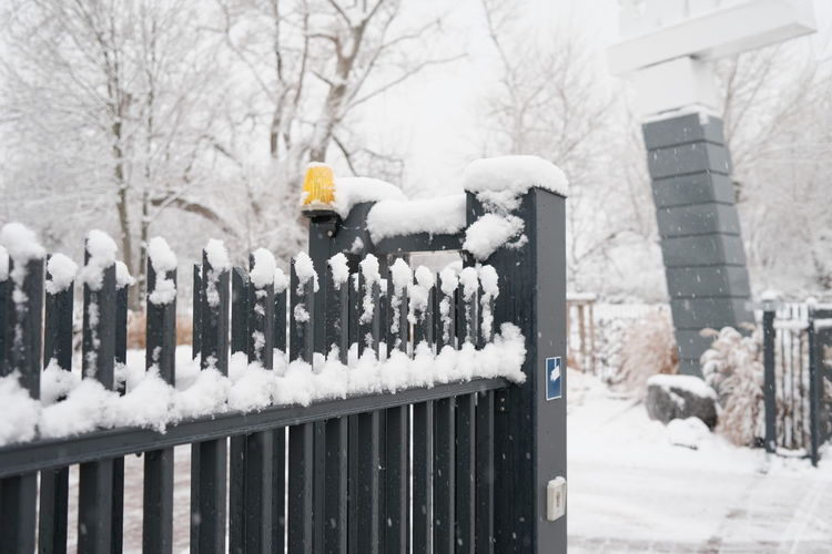 Snow covered fence against bare trees during winter