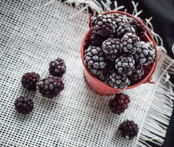 Frozen blueberries in a red bucket on the table in summer 2018