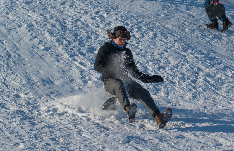 Low angle view of man sliding downhill on steep snow
