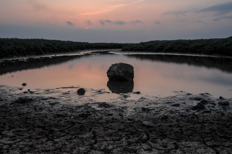 Scenic View Of Rock In Lake Against Sky At Sunset