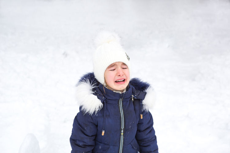 Little girl crying outside in winter. a child in warm clothes is upset, cold, wipes away tears,