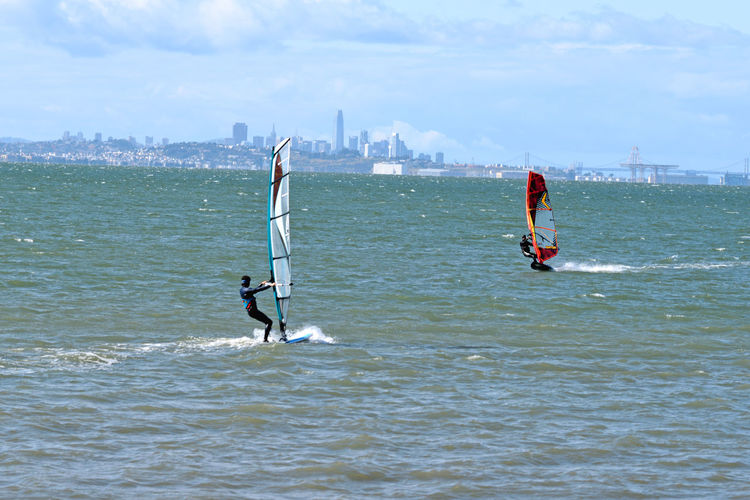 Windsurfing At Coyote Point 14 Windsurfers Windsurfing Coyote Point San Francisco Bay Riding The Winds Men Wetsuits Wind Sails Surfboards Motion Wakes Bay Bridge San Francisco Skyline Hunters Point Battleship Crane Cityscape Sports Photography Aquatic Sports Extreme Sports A Day On The Bay Water Sportsman Adventure Rushing Skyscraper Financial District  Downtown Skyline