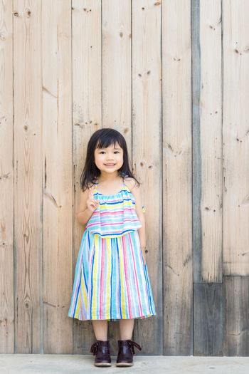Bangs Child Childhood Clothing Dress Emotion Fashion Females Front View Full Length Girls Hairstyle Happiness Innocence Looking At Camera Offspring One Person Portrait Smiling Standing Women Wood - Material