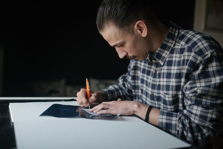 Midsection of man holding smart phone on table