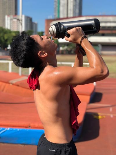 Side View Of Shirtless Sweaty Man Drinking Water While Standing On Sports Track