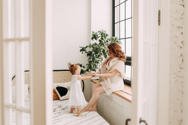 Woman sitting on white wall