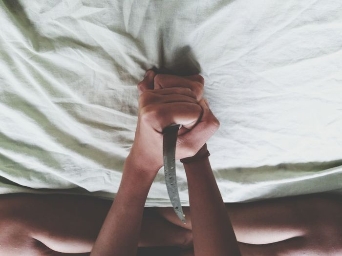 Low section of woman holding knife while sitting on bed at home