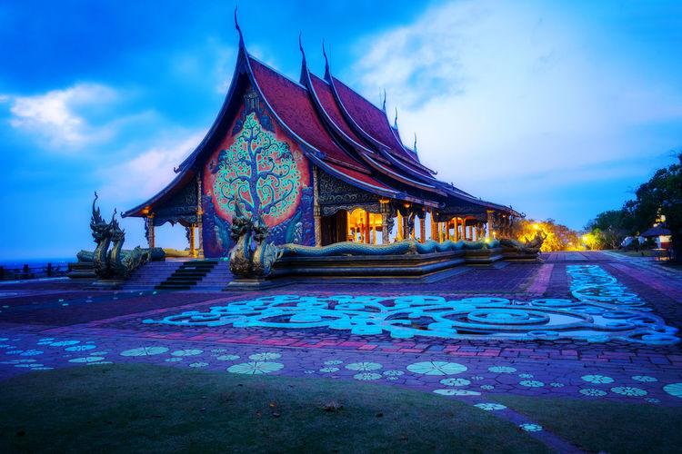 Illuminated temple building against sky