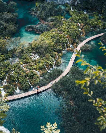 People walk across wooden path over lakes and waterfall at plitvice lakes national park.