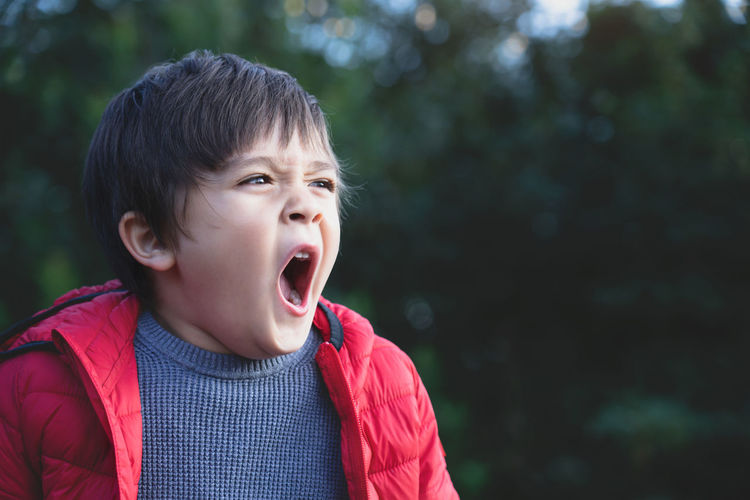Cute boy yawning while standing outdoors