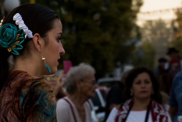 Side view of young woman wearing earring and hair accessory outdoors