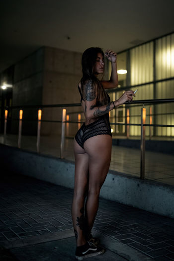 Young woman in lingerie smoking cigarette standing at parking lot