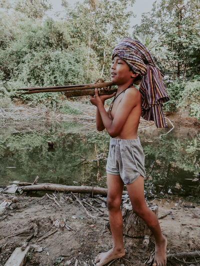 Full length of shirtless boy holding wood while standing against trees in forest