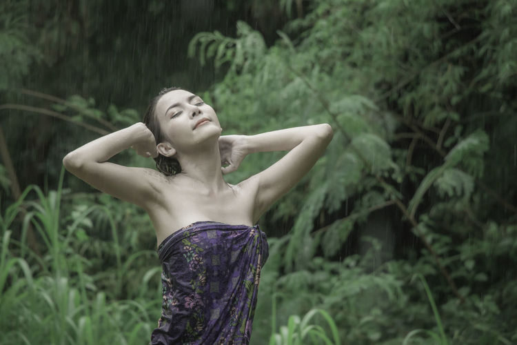 Woman with hand in hair standing outdoors during rainy season