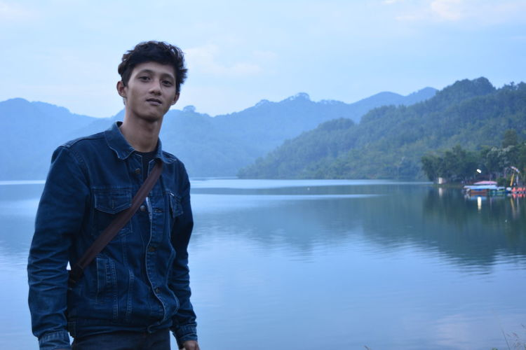 Young man standing by lake against mountains