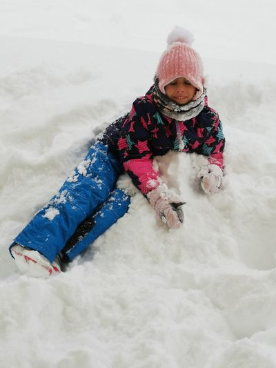 High angle view of girl sitting on snow covered field