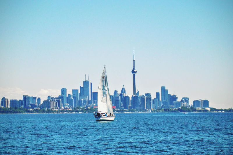 Sailboat sailing in sea by cn tower and city against sky